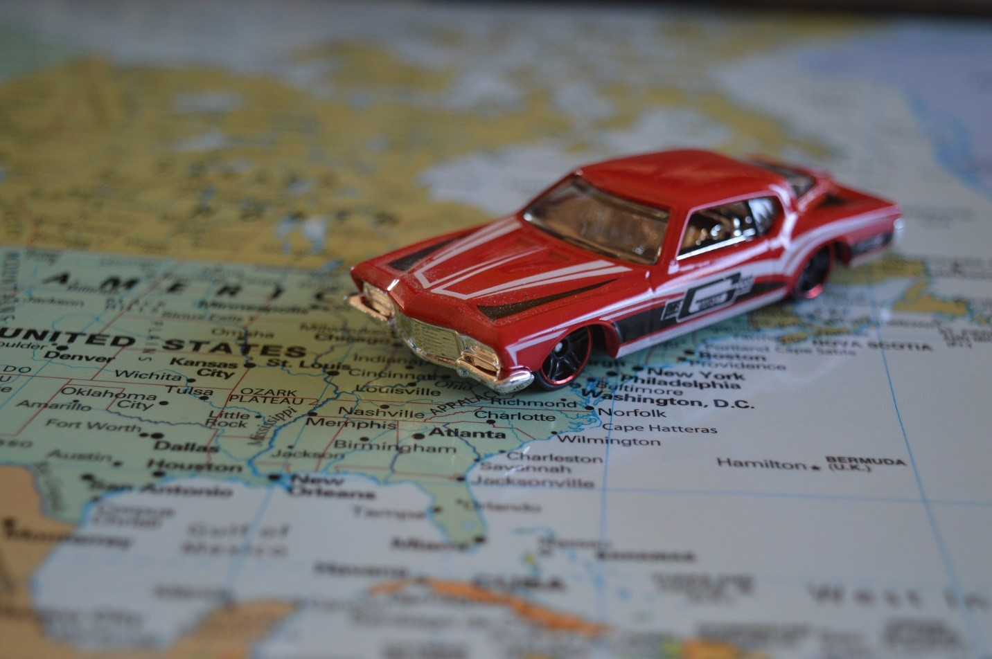 A red toy car on the map of the US